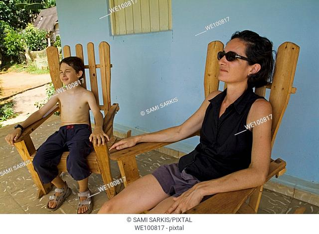 Mother and son resting on a terrace after hiking, Vinales, Pinar del Rio Province, Cuba