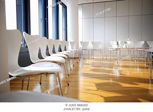 Sunlit room with chairs lining walls