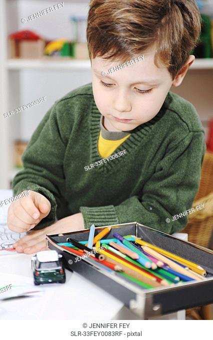 Boy drawing with colored pencils
