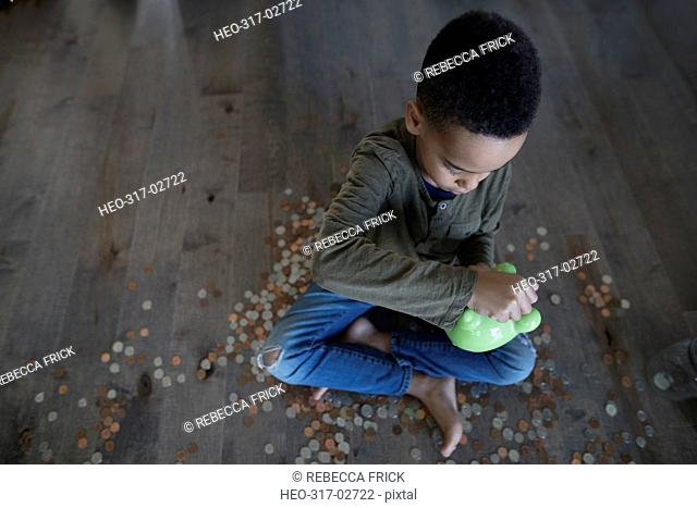 Boy depositing coins into piggy bank on hardwood floor