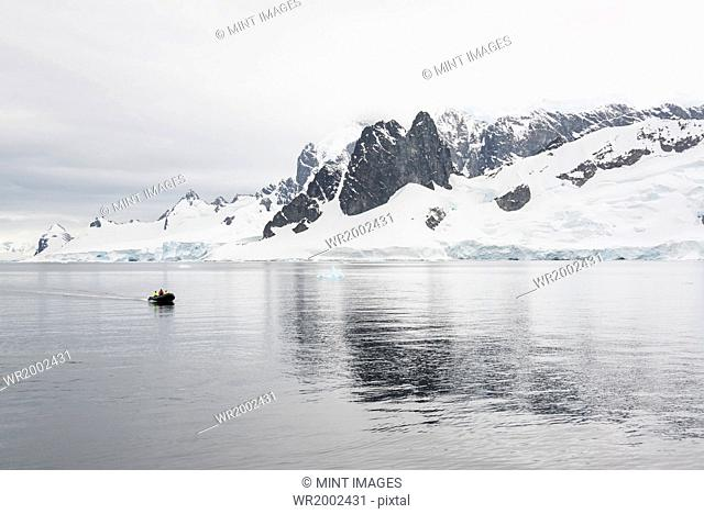 Group of people crossing the ocean in the Antarctic in a rubber boat, snow-covered mountains in the background