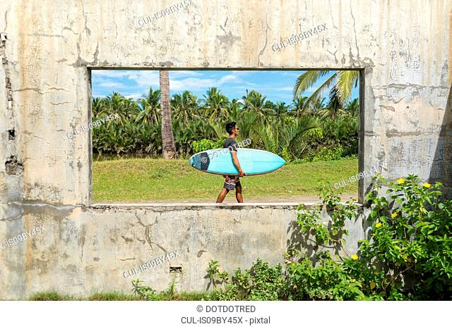 Surfer seen through window of abandoned building, Abulug, Cagayan, Philippines
