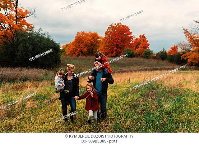 Mid adult family with three daughters strolling together in rural field
