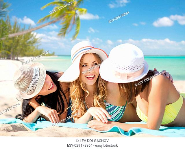 summer holidays, vacation, travel and people concept - group of smiling young women in hats lying over exotic tropical beach with palm trees background