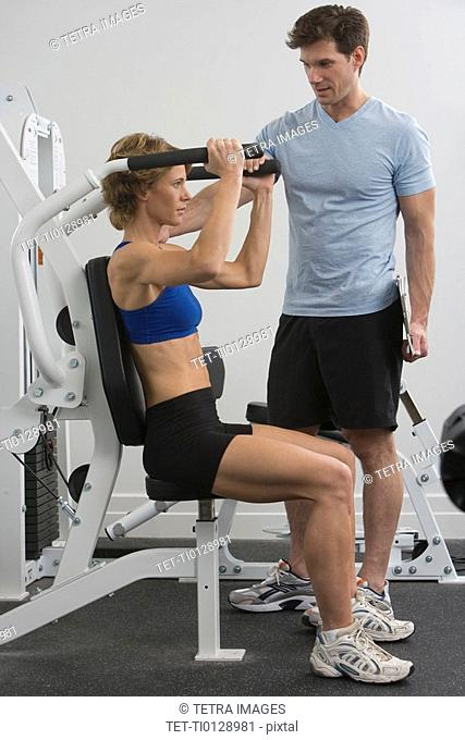 Personal trainer assisting woman on exercise machine