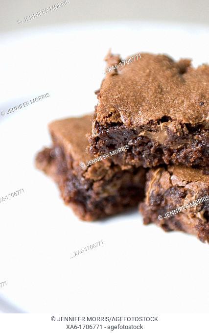 A stack of three gooey, freshly-baked chocolate brownies
