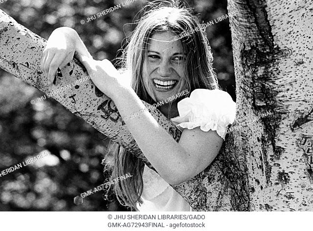 A photograph of a female undergraduate student at Johns Hopkins University laughing and posing with a tree on campus during the first years of the undergraduate...