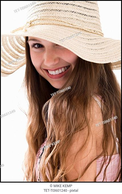 Smiling long haired woman wearing a straw hat