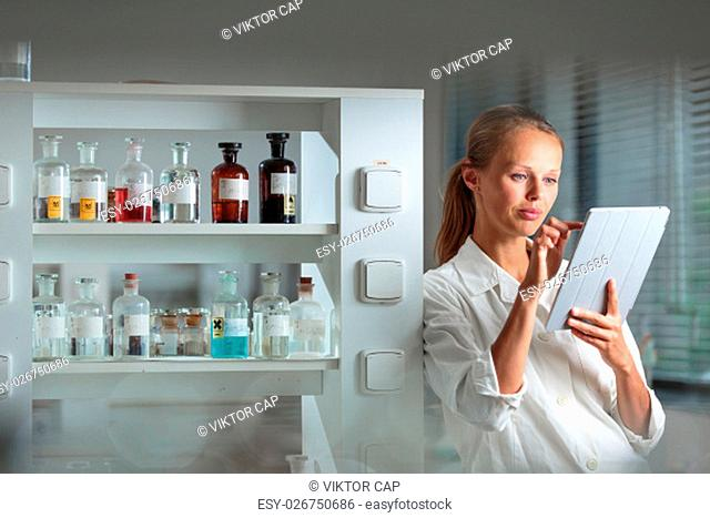 Portrait of a female researcher doing research in a biochemistry lab (shallow DOF; color toned image)