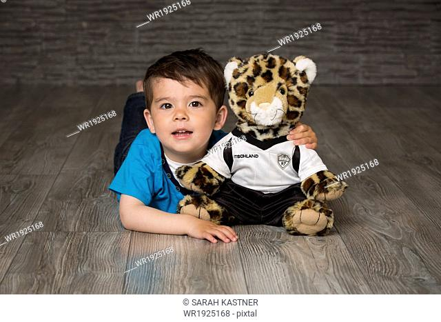 Little boy with cuddly toy on floor