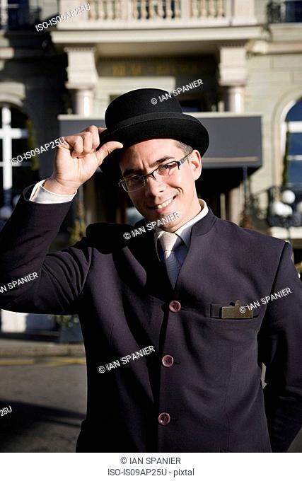 Portrait of polite man holding bowler hat