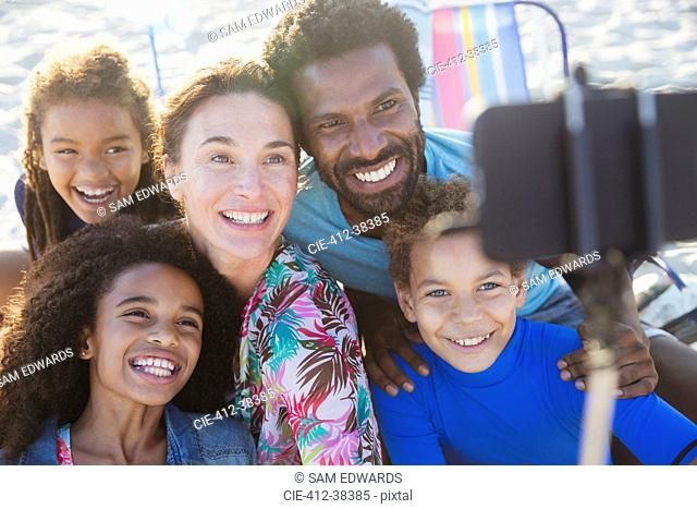 Smiling, happy multi-ethnic family taking selfie with selfie stick camera phone on beach