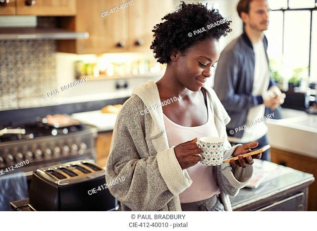 Woman drinking coffee, texting with smart phone in kitchen