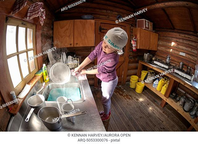 A young girl doing dishes in the Elizabeth Parker Hut, Lake O'Hara, Yoho National Park, Field, British Columbia, Canada