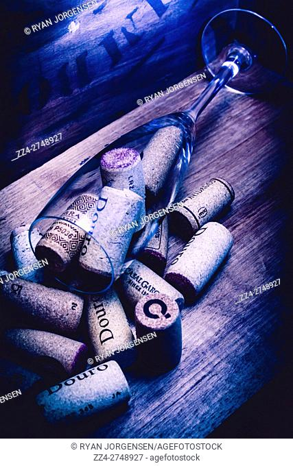 Blue still-life filtered shot of glass full of wine corks on wooden background. Vino tipple