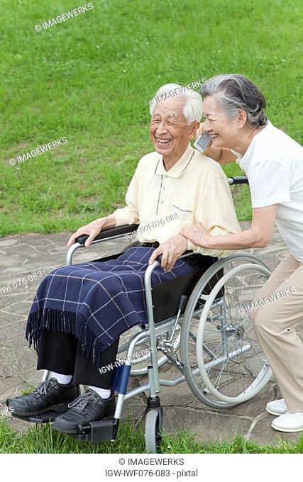 Japan, Tokyo Prefecture, Senior man sitting on wheelchair, woman using mobile phone, smiling