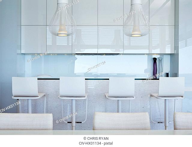 Modern white kitchen with breakfast bar and barstools