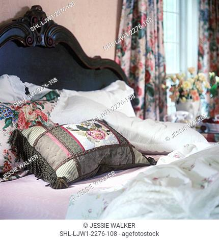 BEDROOM - Detail of decorative pillows on bed with green headboards, floral curtains, flowers in vase by window, soft focus background