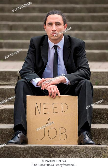 Man in suit sitting at stairs with sign. Unemployed man looking for job