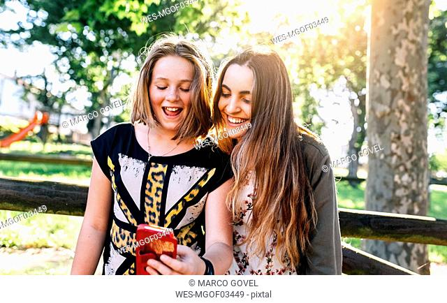 Two girls having fun with their smartphone outdoors