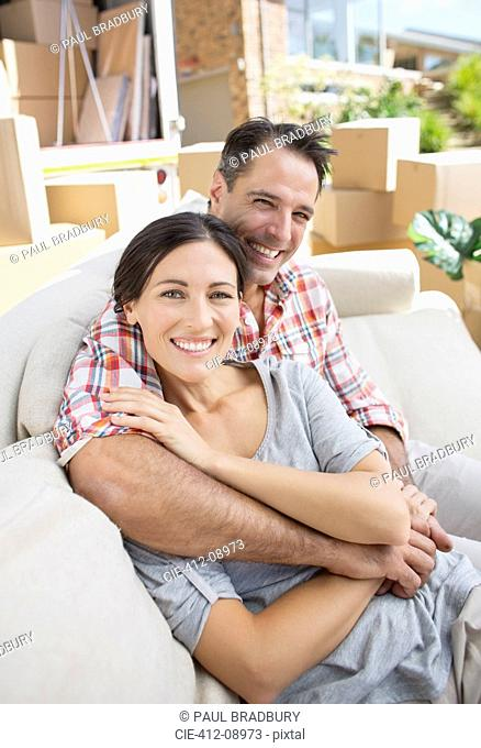 Portrait of smiling couple hugging on sofa in driveway near moving van