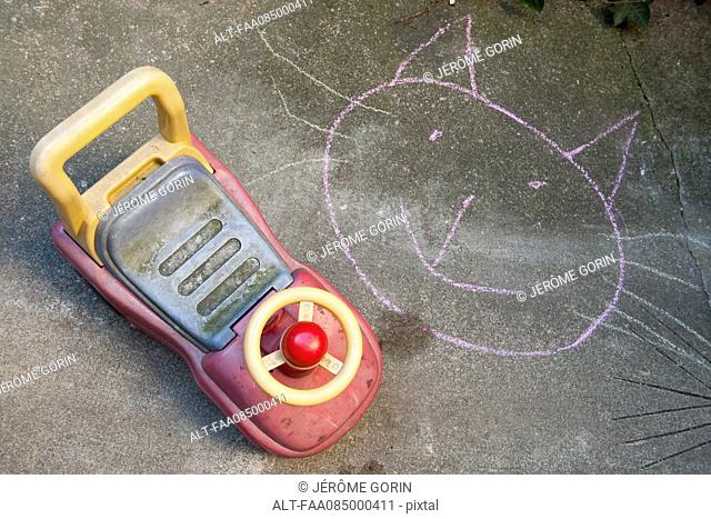Child's chalk drawing and toy car