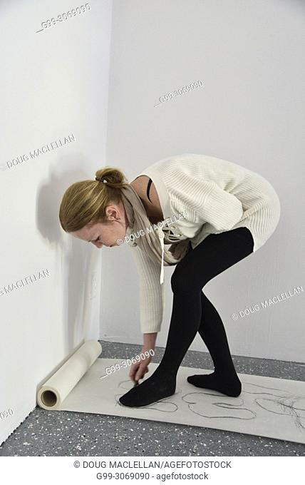 A woman artist bends over to draw on rolled paper as part of a performance art work at an artist run gallery in Windsor, Canada