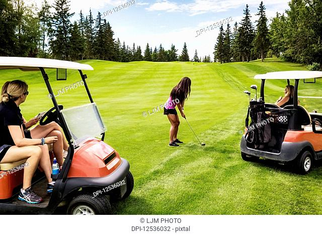 A group of female golfers watching from their golf carts while their teammate is planning her shot out of the rough on a golf course on a warm summer day;...