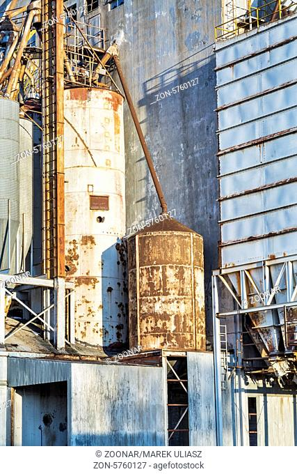 industrial background - exterior of old abandoned grain elevator with pipes, ducts, ladders and chutes