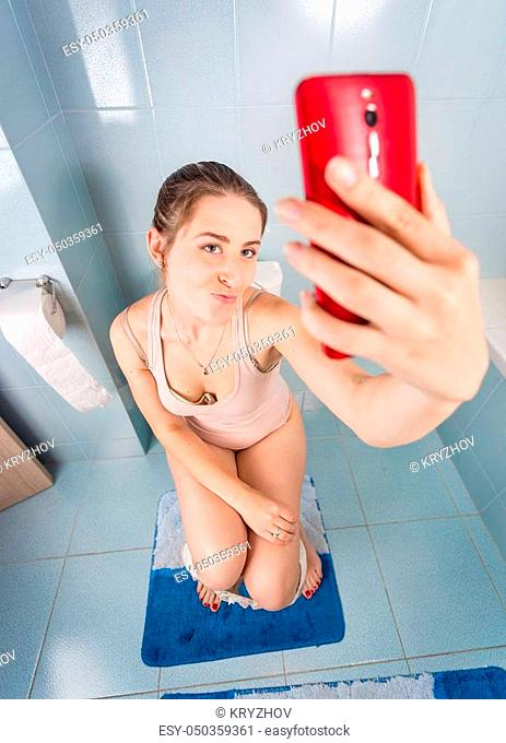 Funny image of young woman sitting on toilet and making selfie on smartphone