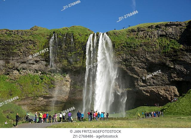 Seljalandfoss waterfall with tourists at Iceland