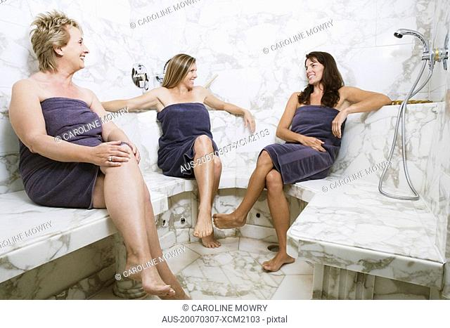 Two mid adult women and a mature woman sitting in the bathroom and smiling