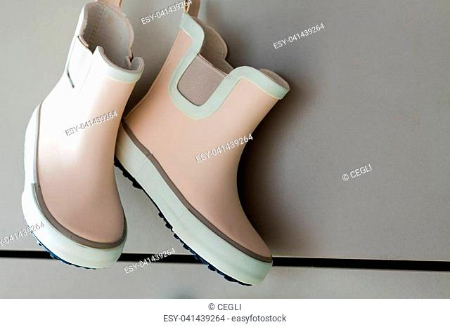 Pink little children rubber boots, concept of autumn or spring background