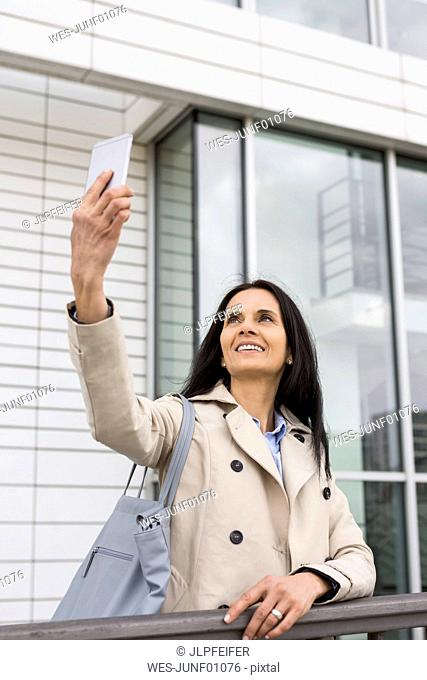 Portrait of smiling woman taking selfie with cell phone