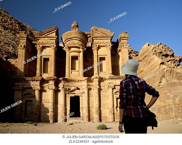 Silhouette of a woman watching the famous and elaborately carved façade of Al Deir (the Monastery), carved out of a sandstone rock face