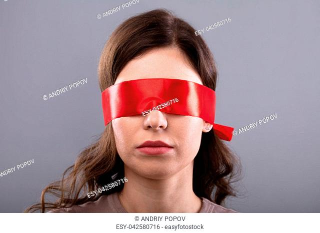 Young Woman's Eye Covered With Red Ribbon On Grey Background