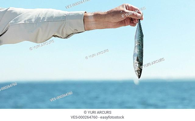Panning shot of a small fish being held out at arm,s length by a senior fisherman smiling at the camera