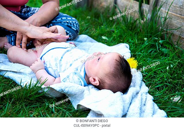 Cropped shot of woman applying cream whilst changing baby son's nappy in garden