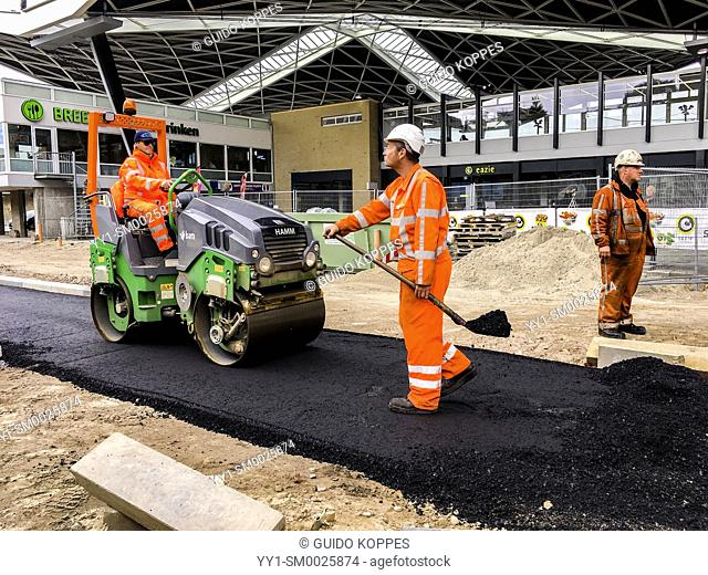 Tilburg, Netherlands. Construction workers building and constructing a new, asphalt road, passing the local railroad station