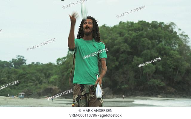 man with dreadlocks and a beard juggling on the beach