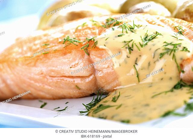 Salmon filet with roasted potatoes and gravy and fresh dill