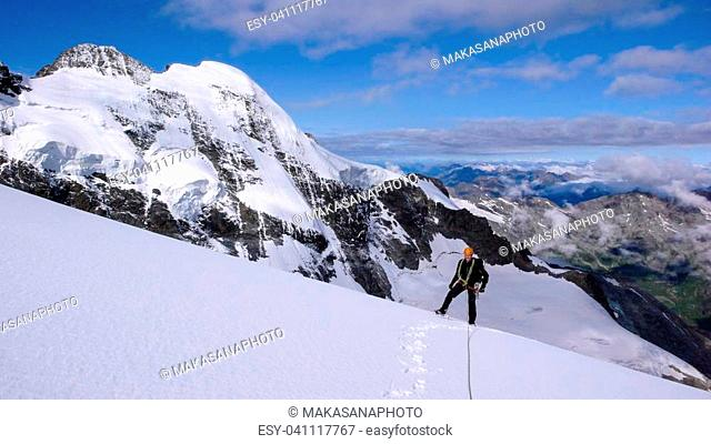 A male mountain climber on a high alpine glacier with a great view of the fantastic mountain landscape behind him