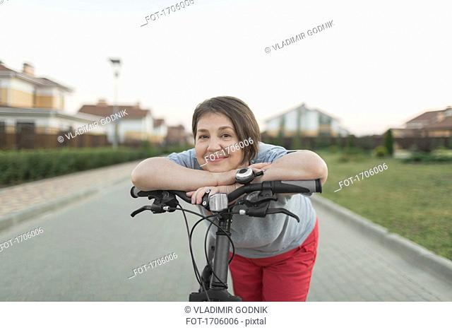 Portrait of senior woman leaning over bicycle handle on street