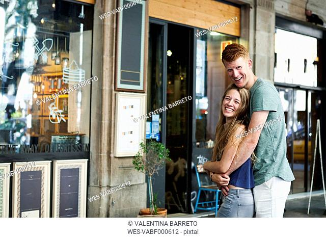 Happy couple standing in front of a coffee shop