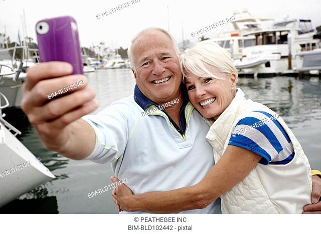 Smiling couple taking self-portrait at marina