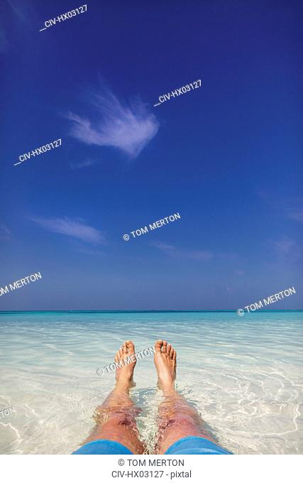 Personal perspective barefoot man laying in tropical blue ocean surf