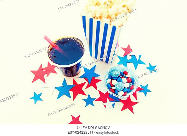 american independence day, celebration, patriotism and holidays concept - close up of coca cola cup, popcorn and candies with stars confetti decoration at 4th...