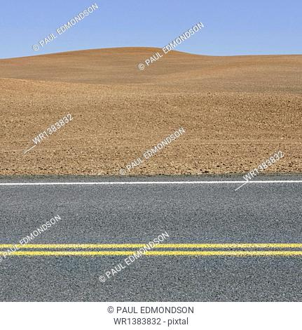 A road through the farming landscape of ploughed fields and farmland near Pullman, Washington state