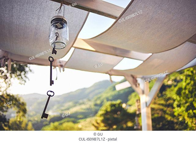 Key wind chime hanging from patio rafter, Lucca, Tuscany, Italy