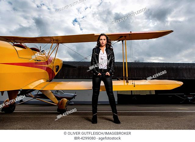 Young woman with leather jacket poses with yellow double-decker aviator, fashion